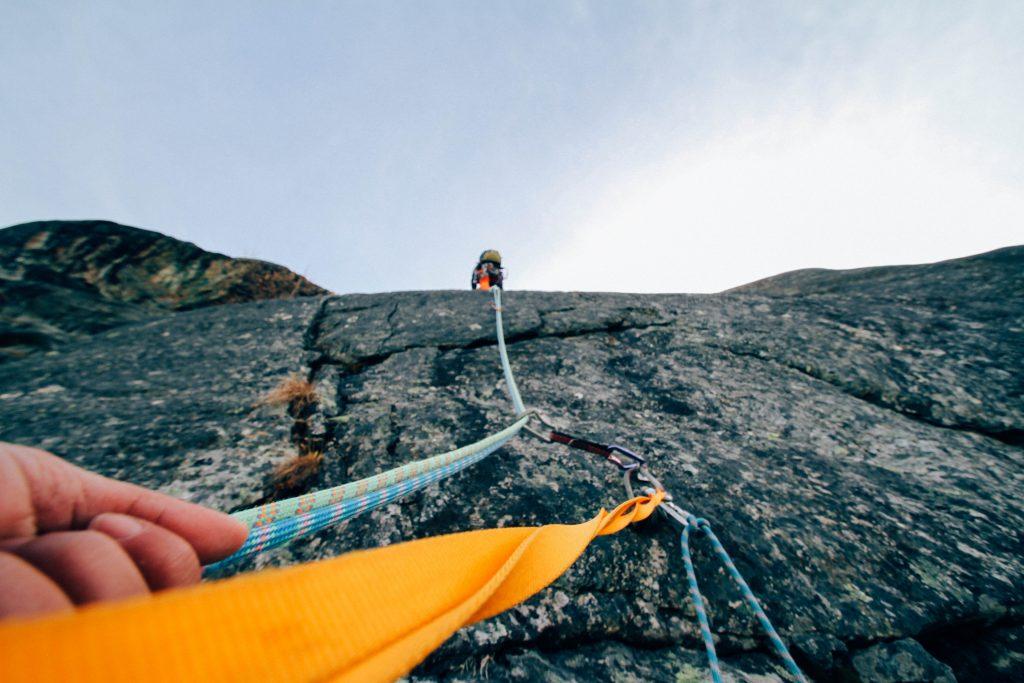 Menschen klettern an einem Seil eine Bergwand hoch
