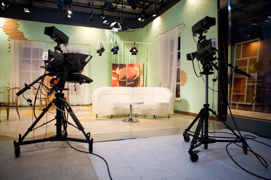 Bild eines ausgeleuchteten Studios mit zwei Kameras und einer weißen Couch in der Mitte