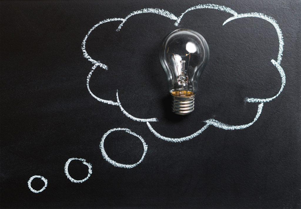 Auf einer schwarzen Tafel ist mit Kreide eine Gedankenblase aufgezeichnet in der eine reale Glühbirne ist