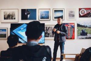 ein asiatischer Mann steht vor einer Bilderwand und neben einem Fernseher. Er hält einen Vortrag vor Zuschauern