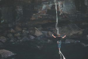 Mensch balanciert über einem Fluss udn zwischen zwei Klippen auf einem Seil