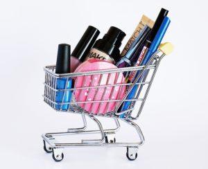 Kosmetikprodukte in einem kleinen Einkaufswagen