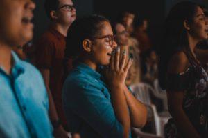 Frau im Publikum freut sich und hält die Hände zusammen