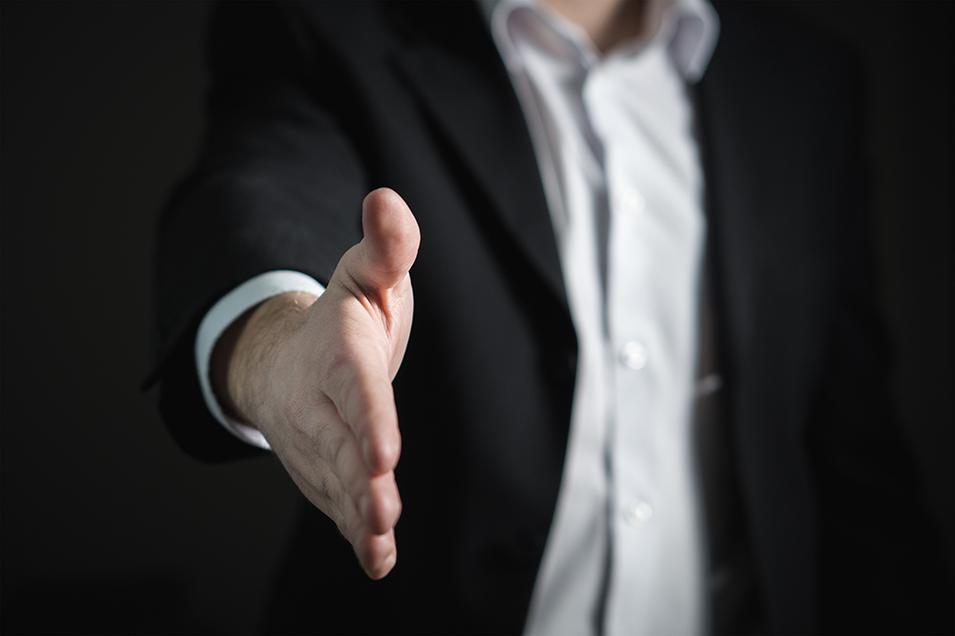 Foto von einem Mann in einem Anzug, der die Hand für einen Handschlag hinhält