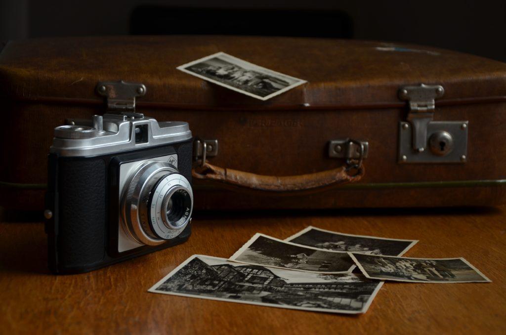 Alte Fotografien und eine alte Kamera stehen auf einer Holzoberfläche vor einem alten Koffer