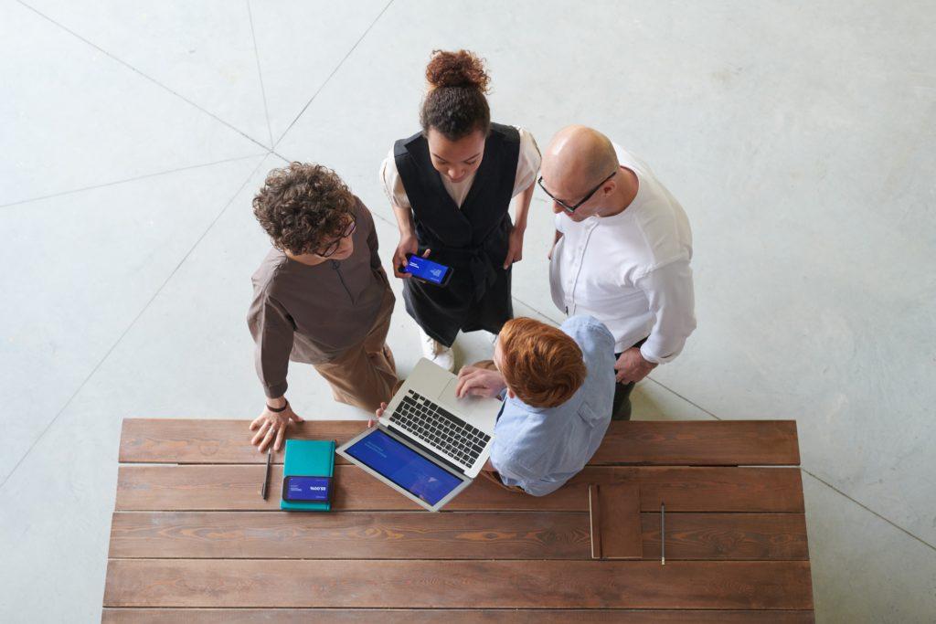 Meeting von vier Personen und es wird etwas auf dem Laptop gezeigt