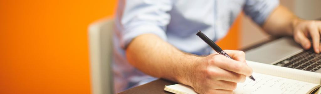 Mann macht sich Notizen auf Papier, während er am Laptop tippt