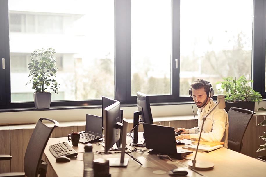 Mann sitzt in einem Büro vor Bildschirmen