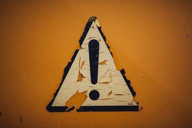 Sticker von einem Ausrufezeichen auf einer Wand, der langsam abblättert