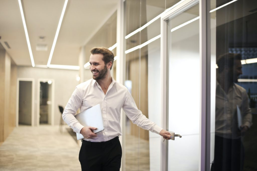 Junger Mann steht in Hemd und Hose vor einem Raum und hält Papiere in der Hand