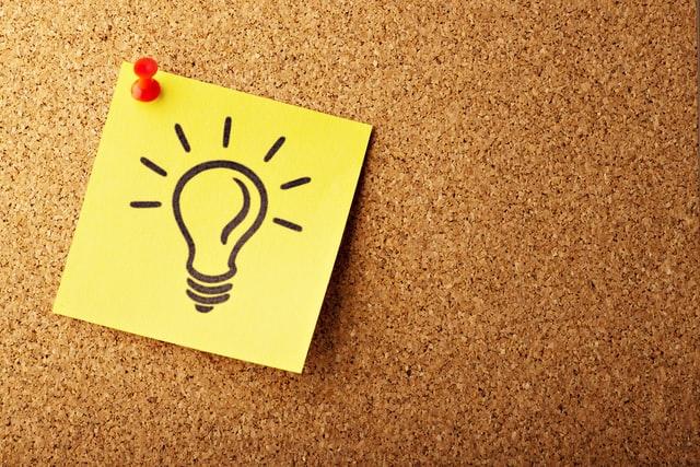 gelber Postit mit einer Glühbirne auf einem Kork Hintergrund