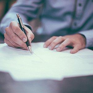 Mann schreibt Inhalte auf Zettel